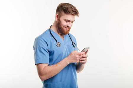 휴대 전화를 사용 하 고 웃 고 흰색 배경 위에 격리 남성 의사의 초상화.