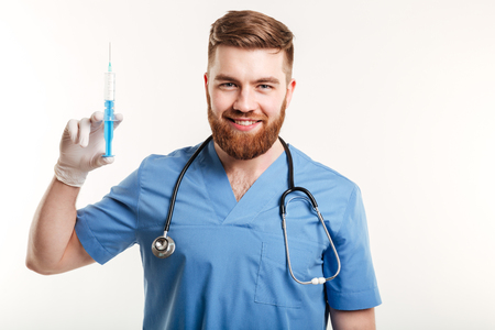 Portrait of a smiling happy medical doctor or nurse holding syringe and looking at camera isolated on white background Stok Fotoğraf