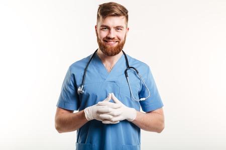 Retrato de un médico o una enfermera masculino feliz sonriente que usa los guantes quirúrgicos y que mira la cámara aislada en el fondo blanco Foto de archivo - 77859213