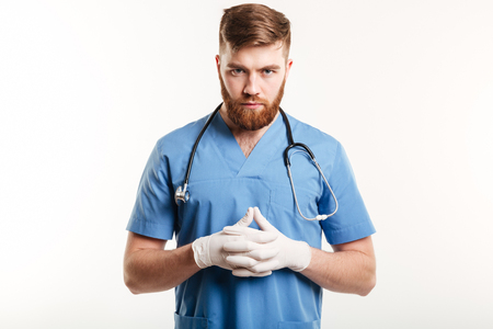 Portrait of a serious concentrated male medical doctor or nurse wearing surgical gloves and looking at camera isolated on white background