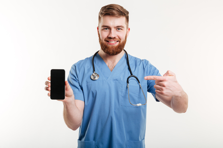 Portrait of male doctor showing blank smartphone screen and smiling isolated over white background. Imagens