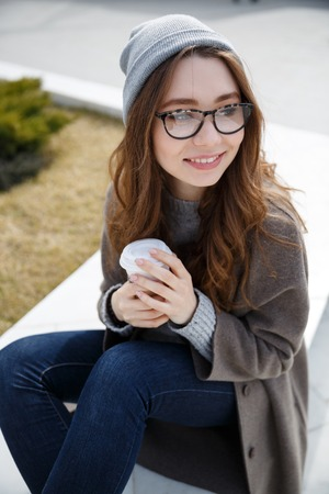 Smiling cute young woman sitting and drinking coffee-to-go outdoors in autumn