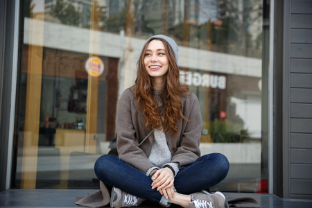 Cheerful attractive young woman in hat sitting with legs crossed outdoors in the city