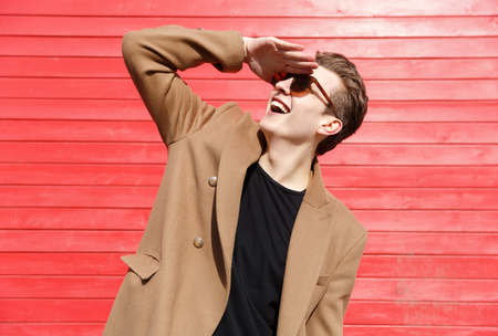 Cheerful young man in sunglasses standing and looking far away over red wall background