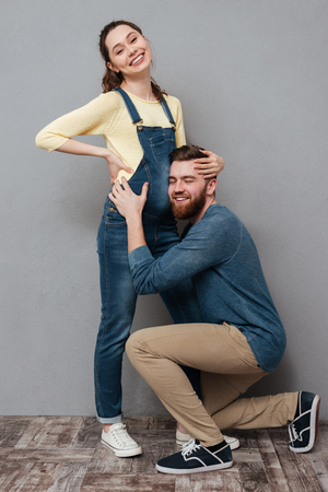 Image of pregnant happy woman hugging cheerful man isolated over grey wall. Looking at camera.