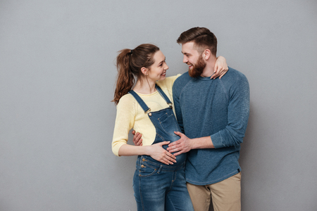 Photo of pregnant happy woman hugging cheerful man isolated over grey wall. Looking aside.