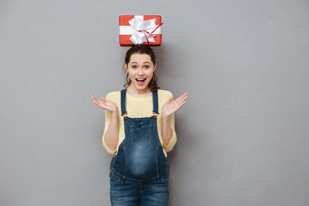Image of pregnant happy lady standing isolated over grey wall while holding gift on head. Looking at camera. Stock Photo