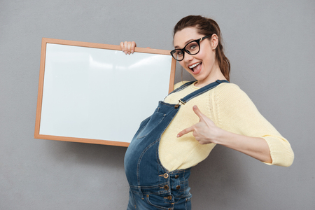 Image of pregnant happy lady wearing glasses standing isolated over grey wall while holding copyspace board and pointing. Looking at camera.