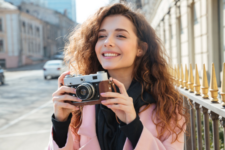 looking away from camera: Photo of a attractive woman in coat holding retro camera while standing on the street Stock Photo
