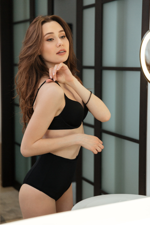 bathroom mirror: Beautiful sensual young woman in black lingerie looking at the mirror in bathroom