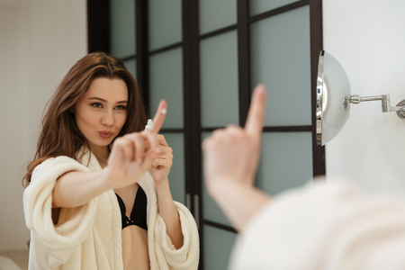 bathroom mirror: Beautiful young woman with cream on her finger looking at the mirror in bathroom