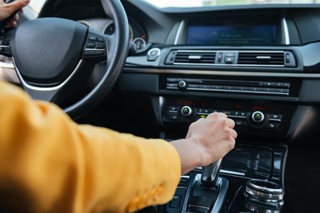 女性ドライバーの車を運転する前に固執するギアをシフトの手のクローズ アップ 写真素材