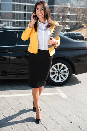 Cheerful young businesswoman in yellow jacket walking and talking on cell phone outdoors Stock Photo