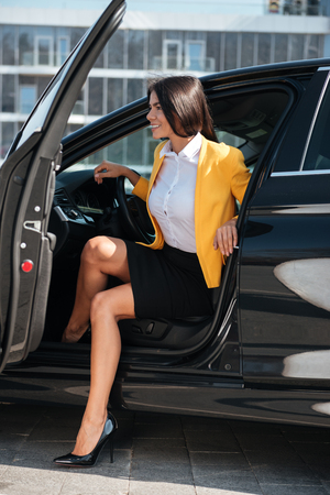 Happy young businesswoman in yellow jacket sitting in the car with opened door Stock Photo - 78084722