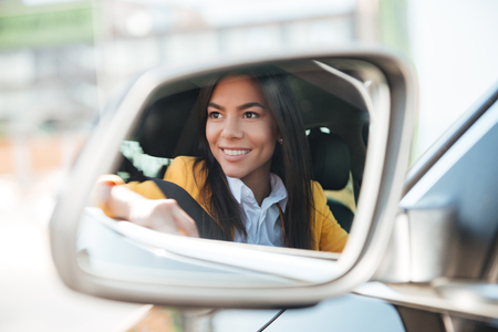 travelling salesman: Reflection of smiling business woman in side view car mirror Stock Photo