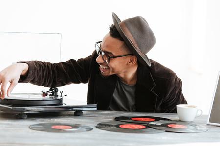 スーツ、眼鏡、帽子、テーブルに座って、レコード プレーヤーを使用しての幸せなアフリカ男 写真素材