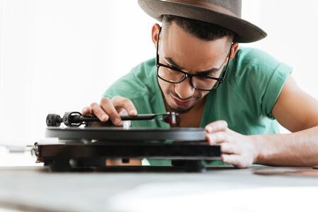 若いアフリカ t シャツ、眼鏡の男し、テーブルに座って、レコード プレーヤーを使用しての帽子です。写真をクローズ アップ