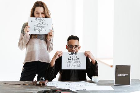 女紙のシートを保持しているとアフリカの近くに立っている男がテーブルに座って、紙のシートを表示 写真素材