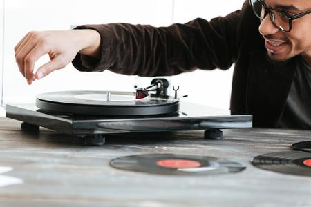 テーブルに座って、レコード プレーヤーを使用してジャケットのアフリカ人間の画像をトリミング 写真素材