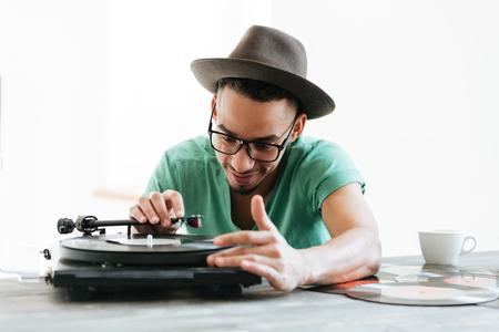 T シャツ、帽子、眼鏡、テーブルに座って、レコード プレーヤーを使用してアフリカ人の人