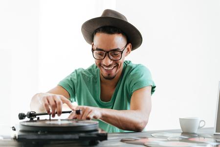 T シャツ、眼鏡、帽子、テーブルに座って、レコード プレーヤーを使用してアフリカ人の笑顔 写真素材