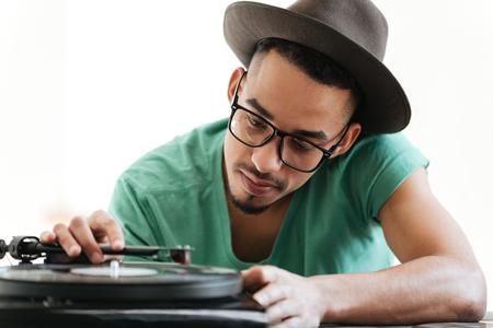 T シャツ、眼鏡、帽子、テーブルに座って、レコード プレーヤーを使用してください。 アフリカ人の人を集中してください。 写真素材