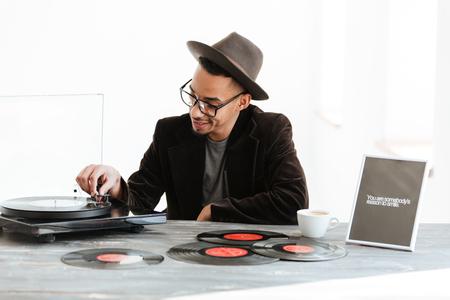 帽子、スーツ、眼鏡、テーブルに座って、レコード プレーヤーを使用してアフリカ人の人 写真素材
