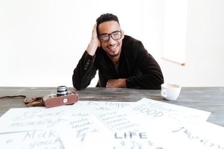 スーツと眼鏡、カメラを見ながら一杯のコーヒーとレトロなカメラ付きのテーブルで座っているアフリカ人 写真素材