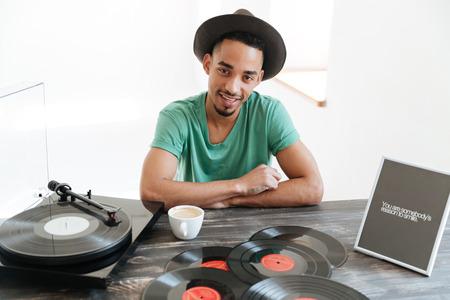 緑の t シャツと帽子のレコード プレーヤーと多数のレコードを持つテーブルで、カメラを見ながら座っているハンサムなアフリカ人