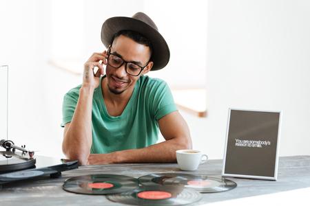 T シャツ、帽子と眼鏡、テーブルに座って、スマート フォンで話している若いアフリカ人