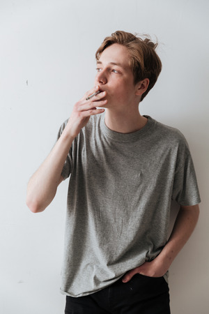 Vertical image of a young man in t-shirt smoking cigarette and holding arm in pocket over gray background Stock fotó