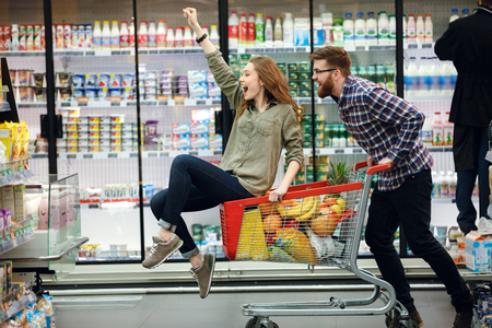 Happy couple having fun while choosing food in the supermarket. Young happy man pushing shopping cart with his girfriend inside Stockfoto