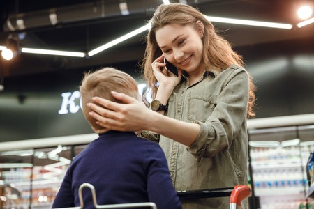 Young beautiful woman mother caressing her sons head while he sitting in cast in shopping centre