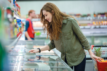 Young brunette woman choosing products it the fridge of supermarket Stock Photo