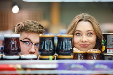 Leuke vrouw en man zitten in de buurt van plank met marmelade in winkelcentrum Stockfoto