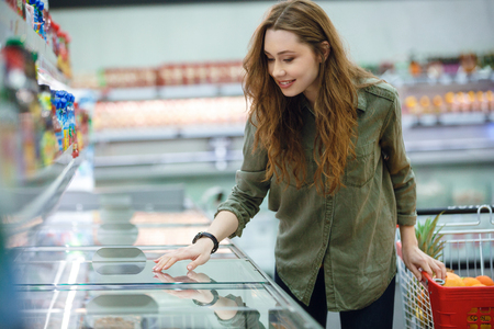 Cute woman with cart looking at products in fridge in supermarket