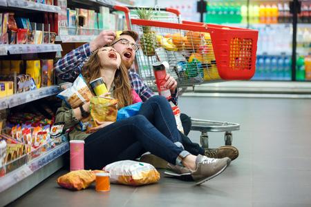 Handsoma Mann geben Chips selbst und seine Frau sitzt im Einkaufszentrum auf dem Boden