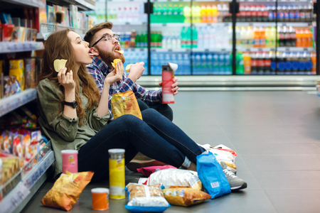 Portrait of a young funny hungry couple sitting on the supermarket floor and eating junk food