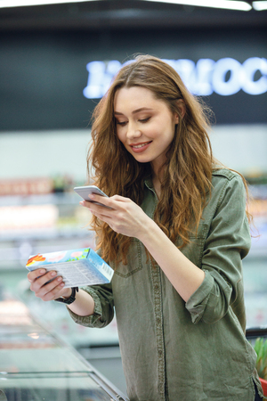 Shot of funny brunette woman photographing product in supermarket