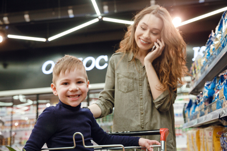 lady on phone: Smiling boy looking at camera which sitting in shopping trolley while his mom talking on smartphone on background Stock Photo
