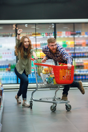 Young happy couple with food cart doing grocery shopping together at the supermarket