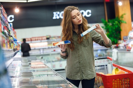 Young woman buyer trying to make choice between two products in shopping centre