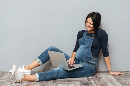 Picture of cheerful pregnant lady sitting on floor over grey background. Looking aside and using laptop computer.