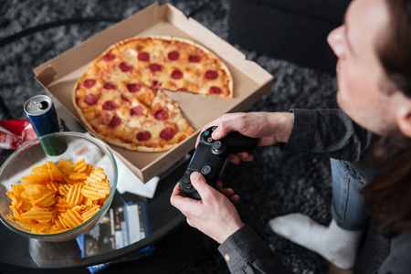 Cropped photo of young man gamer sitting at home indoors and play games with joystick near pizza and crisps. Stock Photo