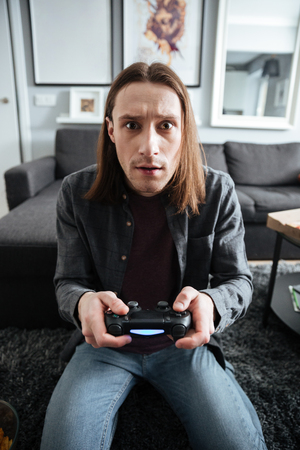 Photo of young concentrated man sitting at home indoors play games with joystick. Looking at camera.