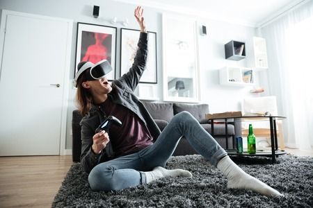 Image of young happy man sitting at home indoors play games with 3d virtual reality glasses. Looking aside.