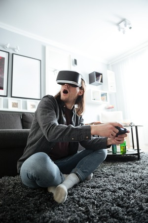 Photo of young concentrated man sitting at home indoors play games with 3d virtual reality glasses. Looking aside.