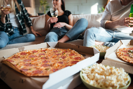 Groep gelukkige jongeren die pizza, thuis het drinken van wijn en bier op bank eten