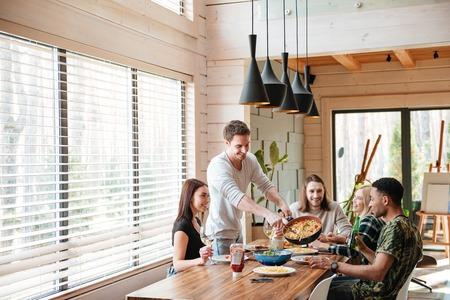 Gruppo di giovani allegri mangiare pasta e parlare al tavolo in cucina