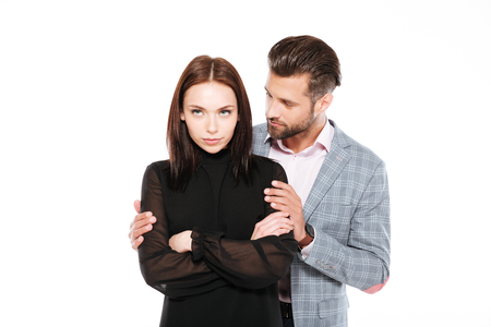 Image of offended young loving couple standing isolated over white background. Looking aside. Man ask for apologize. Stock Photo